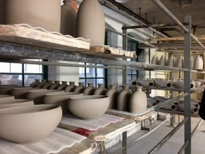 Inside Middleport Pottery, unfired ceramic vessels and bowls wait side-by-side on shelves to be fired.