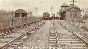 Photo of Oneida Rail Station – a late nineteenth century crowd gathers around a train, ready to board.