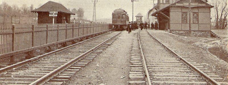 Photo of Oneida Rail Station – a late nineteenth century crowd gathers around a train, ready to board.