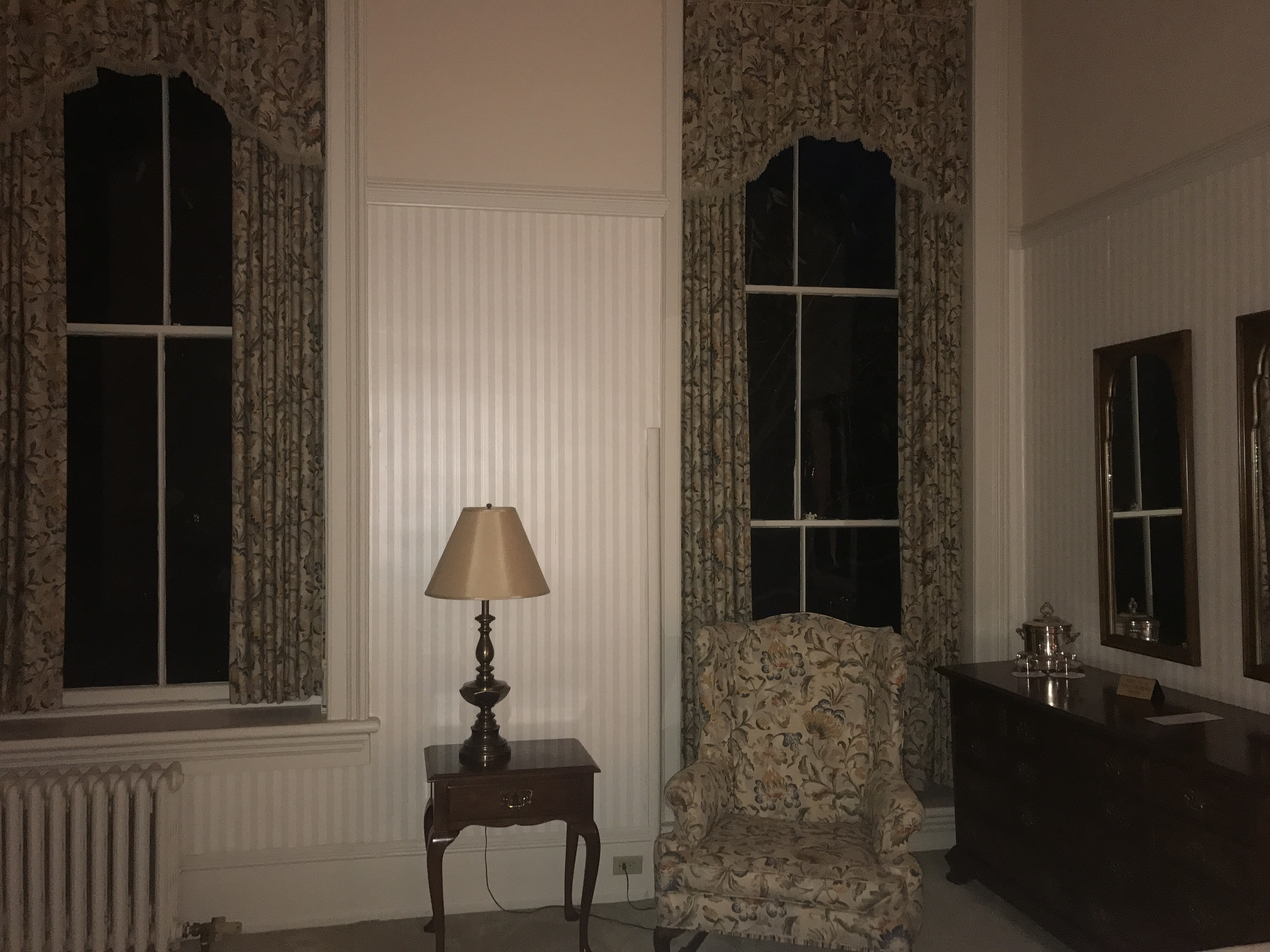 Oneida Room – A bedroom available for overnight stay in the Mansion House features very high ceilings, floral curtains, striped wallpaper, and an easy chair.
