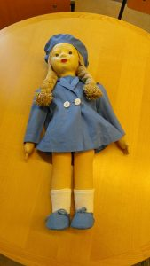 A doll with pale face and blonde braids is laid on a tabletop wearing a light blue coat with two white buttons, matching blue cap and shoes, and white calf-high socks.