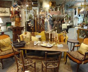 Interior of the antique store. Rectangular table in the center with two upholstered chairs on each side, two wooden chairs in the front. Many candlesticks and small cups sit atop table.
