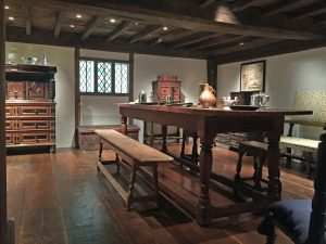 1.The Hart Room at Winterthur holds a variety of 17th century objects, pictured in situ here. The form is next to a large table. Various plates, tankards, and utensils rest on the table. The beamed ceilings and a paned window is also visible in this picture.