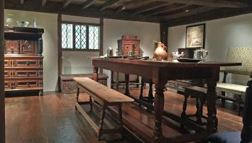 1. The Hart Room at Winterthur holds a variety of 17th century objects, pictured in situ here. The form is next to a large table. Various plates, tankards, and utensils rest on the table. The beamed ceilings and a paned window is also visible in this picture.