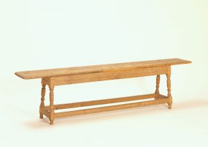 2.Wooden form on white background. The form is comprised of four turned legs with connecting rails. The seat rests atop the legs and has a significant overhang.