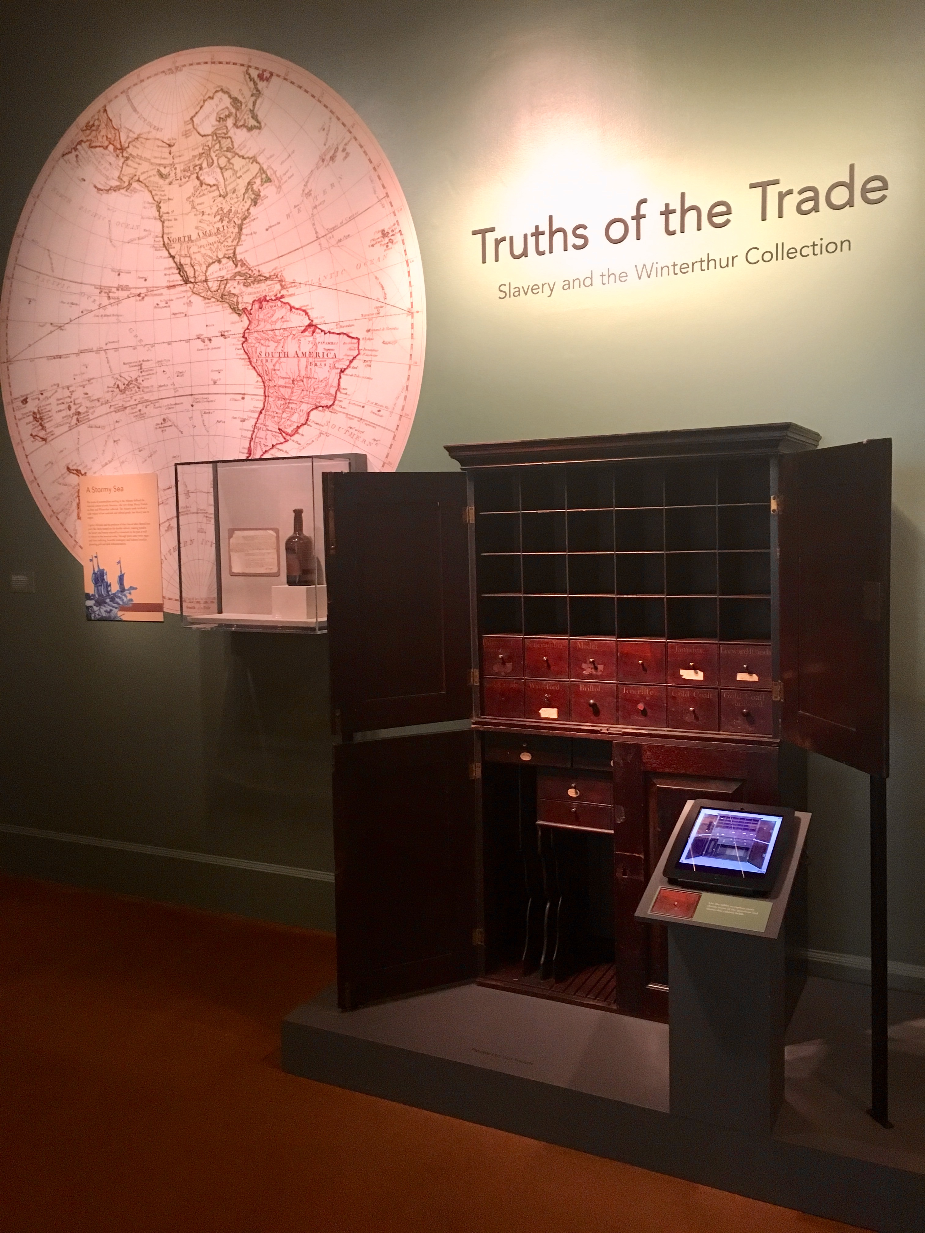 A view inside the Truths of the Trade exhibit featuring the mahogany double cabinet at center along with the the ipad touch screen interactive in the front.