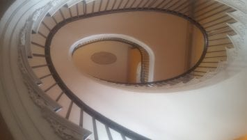 Looking up from the ground floor through the center of a oblong-shaped spiral staircase to the third floor, showing a medallion on the ceiling of the top floor.