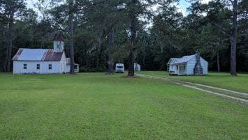 In a landscape of several tall pines and a dirt track between grass are four buildings in the distance. On the left are a church and dwelling with a porch, while on the right is a dwelling with a porch and a cabin without a porch. All buildings are painted white with rusting, white-painted metal roofs. Brick chimneys are visible on the two dwellings on the right.