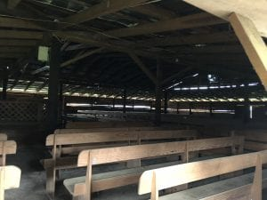 image of tabernacle's interior at Shady Grove Methodist Campground. Wooden construction with wooden pews resting on sand. Pulpit and altar, both wooden, are to the left of the image