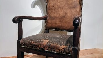 A photograph of an armchair displayed in the Dianne H. Furr Moravian Decorative Arts Gallery at the Frank L. Horton Museum Center. The armchair has dark wooden arms, legs, and front chair rail. The leather on the seat appears dark and worn. The leather on the backrest appears lighter in color than that on the seat. Small brass tacks hold the leather to the wood.