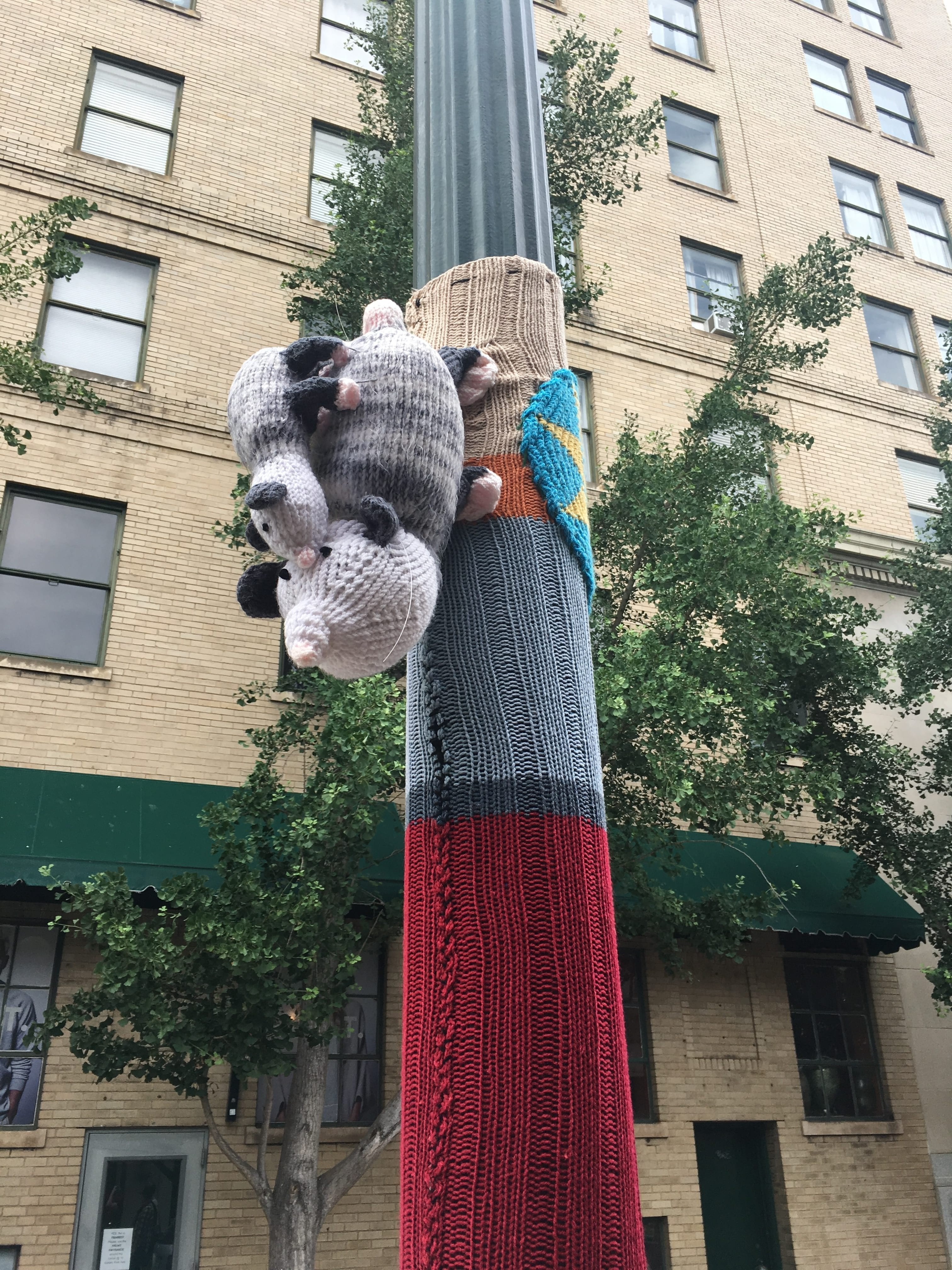 """Knitted and crocheted yarn wraps around a lamp post on a city street. A knitted pair of possums, a mother and a baby, are mounted on the lamp post as well. In the other photograph, a pink and red crocheted fabric has been wrapped around a lamp post. Stitched in the center of a large pink heart are the words, """"Go Local."""""""