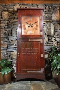 """A large wooden tall-case clock stands before a gray stone fireplace. Inscribed on the case is """"Not enjoyment, and not sorrow/Is out destined end or way; But to act, that each tomorrow/Find us farther than today."""""""