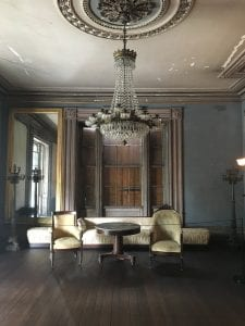 A large, dark room with a crystal chandelier and walls painted in a chalky blue paint.  A few pieces of nineteenth-century furniture stand at the far side of the room.  The grey ceiling paint is chipping, revealing white plaster beneath.