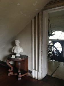 A marble bust of a woman in mid-nineteenth-century dress stands in a grey hallway with chipping paint.  A doorway to another room shows a glimpse of a black ironwork stair railing.
