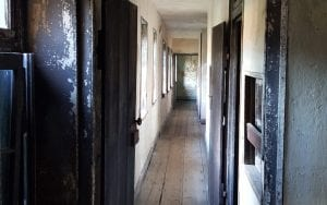 A view down a long, narrow corridor shows the bare plaster walls of a slave dwelling.  The walls are covered in chipped white paint.  At the end of the corridor is a wall covered in chipped mint-green paint.