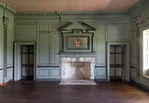 View of an eighteenth-century interior with a central marble mantle flanked by two doorways.  The wood-paneled walls are painted in a worn pale green paint and a painting of a heraldic shield is hung above the empty fireplace.