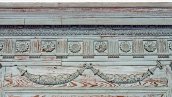 A close-up view shows an intricately carved wooden crown molding with heavily worn blue-green paint.