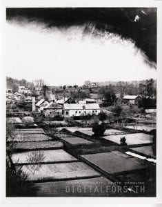 This photograph depicts part of the village of Salem. In the foreground are gardens and in the background are buildings. Trees scatter the landscape and walkways separate the different gardens.