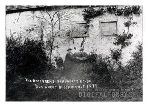 A man in a hat is photographed pointing at a drainage spout coming out of the old slaughterhouse in Salem. The man is standing outside of the building. Bushes and vines are overgrown and are covering part of the exterior.