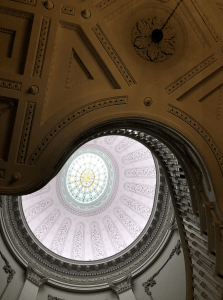 A photograph of a white neoclassical ceiling and staircase with green and yellow stained-glass roundel in the center.