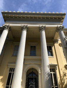 Four classical columns in front of a Greek revival building on a sunny day.