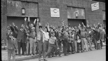"""A group of children standing in front of the brick facade of Fenway Park. Several of the children have their hands raised and look excited. On the facade are two signs that read, """"C Bleachers."""" Large doorways into the baseball park can also be seen."""