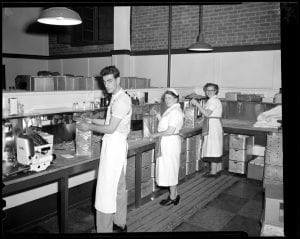 Three people in white aprons working in a kitchen at Fenway Park. Each of the individuals is holding a stack of hot dogs. The kitchen is large and industrial. Two of the individuals are female and one is male.