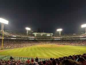 Fenway Park at night. Four stadium lights are on and players are standing in the field. A large crowd has filled the stands.