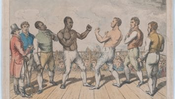A hand-colored etching by George Cruikshank depicts the fight between Tom Molineaux, depicted on the left, and Tom Cribb, depicted on the right. They stand with fists raised ready to fight and are surrounded by five men in the ring. In the background a massive crowd come to watch the match is visible.
