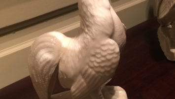 A photograph of a white porcelain rooster with its beak open.