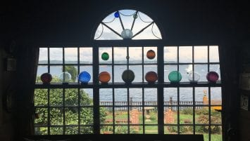 A window, through which a garden and harbor can be seen. Displayed in the window are multicolored glass orbs intended to catch the light.
