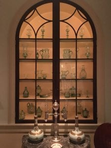 An arched, backlit window with five shelves of green glass bottles, candlesticks, and pitchers.