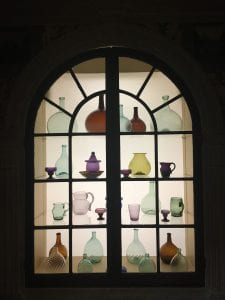An arched window contains four shelves of multicolored glass objects, including green, purple, and brown cups, pitchers, and bottles, that are scattered in an intentional, but seemingly random, order.