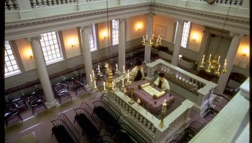 Interior image of Touro Synagogue looking down from the second floor. Bimah located in the center-right with two rabbis viewing a Torah