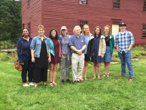 Nine people pose for a group photo. In the background stands a red clapboard colonial home.