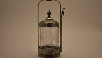 Pressed glass jar with engraved metal lid, stand, and tongs with talon grabbers and an eagle's head hook.