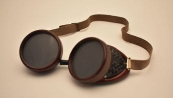 image of single pair of goggles. Dark green tinted lenses with a ridged outer rim; sides feature a metal mesh screen set into a Bakelite google frame. Adjustable elastic band connected to each side of the Bakelite frame.