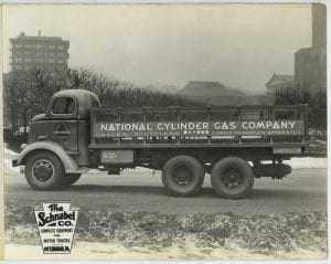"black and white film photograph of a truck with ""National Cylinder Gas Company"" written on the side of the bed of the truck. Truck situated in a semi-urban landscape."