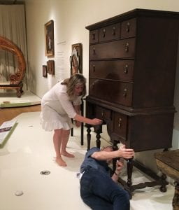 Two people study a piece of brown case furniture in a museum display. Karina Corrigan bends down to touch one of the drawers, while Greg Landry lies on the floor, studying the piece from below.