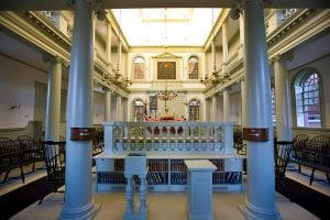 Photograph taken from the entrance of the Synagogue at the back of the space. Columns with ornately carved capitals surround both the regular seating areas and balcony seating, with arched windows on both levels. The Bima is surrounded by turned spindles supporting a wide railing, and the Torah ark is visible in the far distance with the door to the Torah's cupboard open on the left.