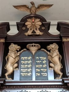 Close-up image of carved mahogany Torah ark with gilt lions on either side of Hebrew words and the Priestly Blessing above. The Priestly Blessing is two hands with thumbs and first fingers touching, then first and second fingers together and ring and pinky fingers together separately. The entire ark is surmounted by two gilt Stars of David and an Eagle with winds spread.
