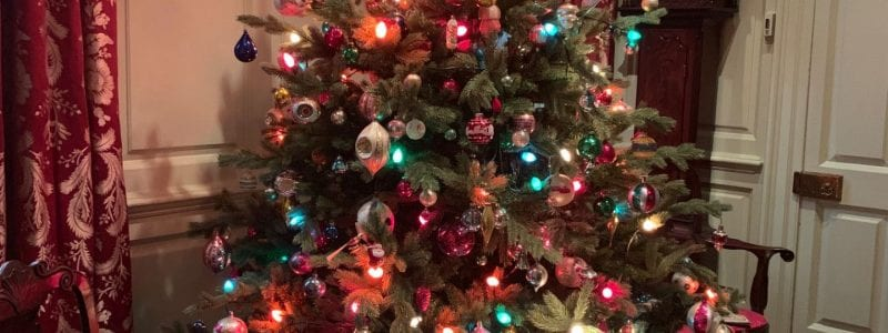 A Christmas tree with multicolored lights and ornaments, with woven market baskets beneath. Inside the baskets are many gift-boxes, each wrapped with a variety of colors of cellophane.