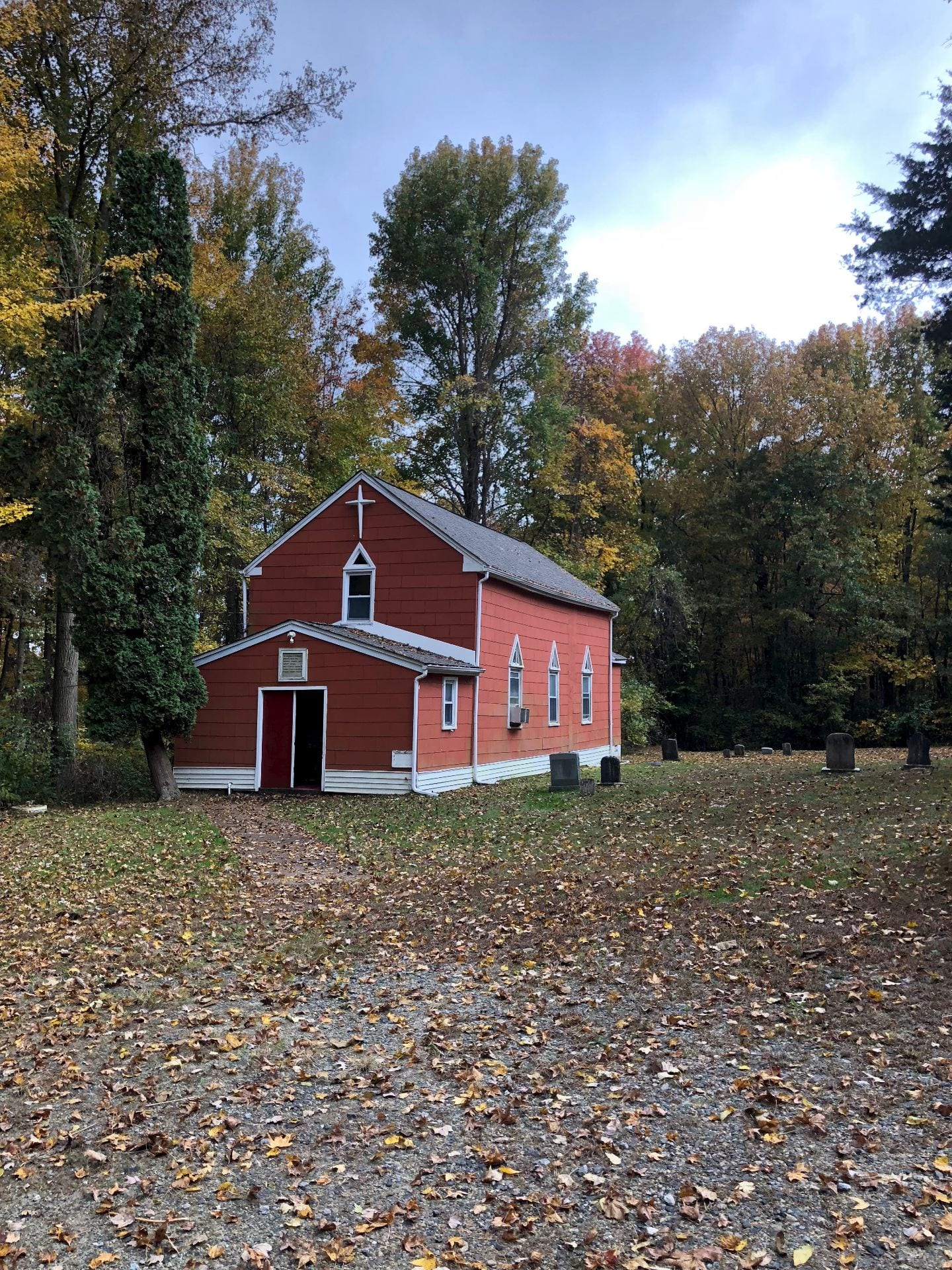 A red church with white trim. To the right of the church are a series of gravestones. Tall trees just beginning to turn for autumn surround the area.