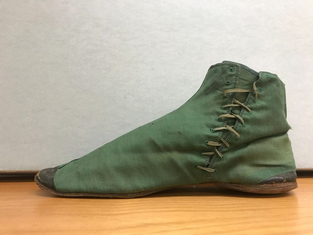 The right shoe of a pair of green ladies' half boots, rising to the ankle with green shoe laces up the inside of the shoe. Black leather shoe toe and heel.