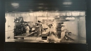 A woman wearing a white cook's hat frosts a cake in the middle of a 1930s professional bakery kitchen.