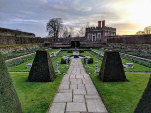 A long rectangular garden with several levels that sink down to a central fountain. The garden's grass, plants, and shrubs are green. Several small statues stand in the garden. In the background is a brick building known as the Banqueting House.