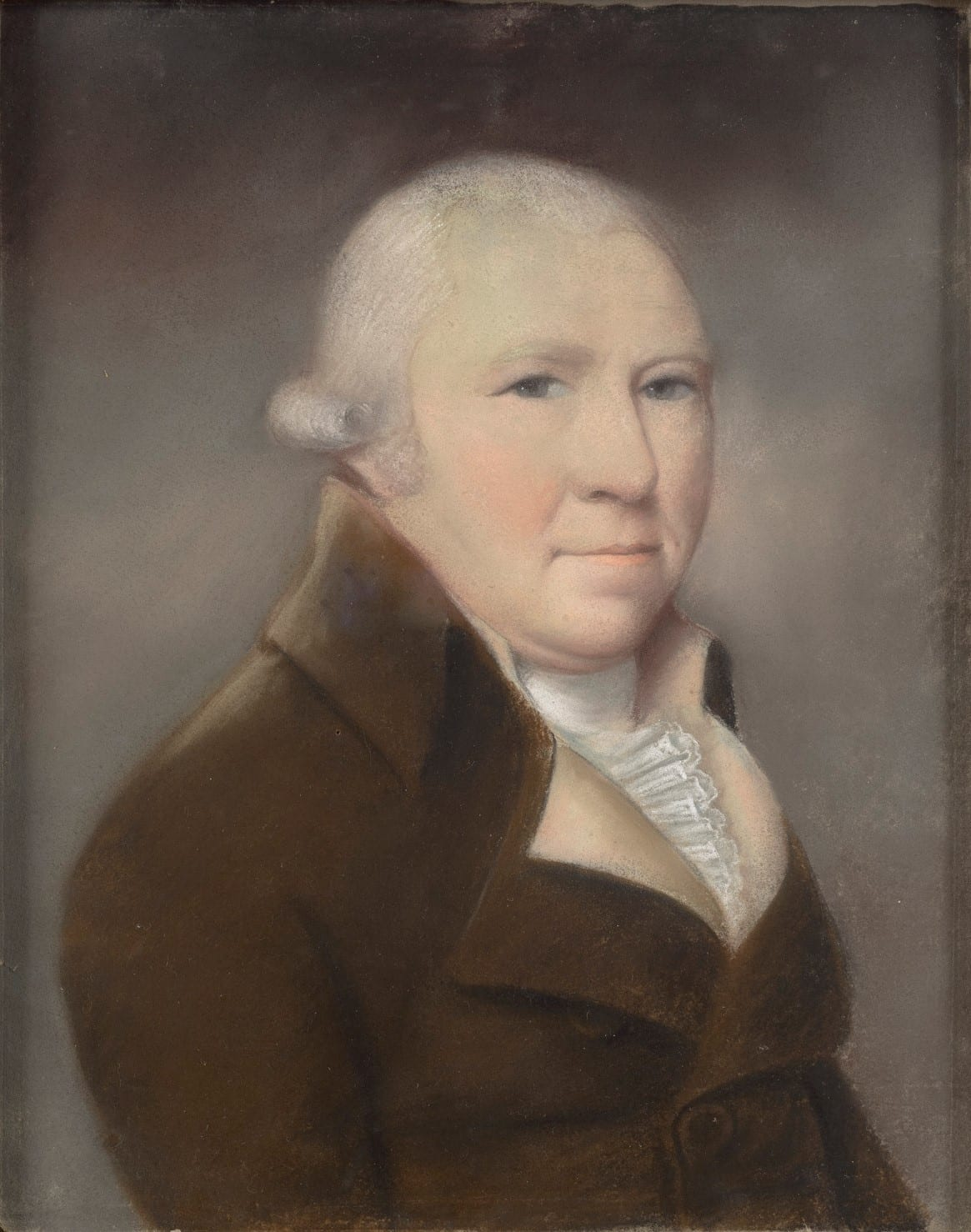 A man with white hair wearing a brown coat sits in three quarter view against a gray background.