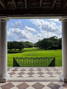 Photograph was taken looking off the portico. Partially visible is the tiled floor of the porch and two pillars that are holding up the portico roof. Two sets of stairs with black iron rails lead down to green grass. In the distance are large trees that flank a road. A body of water is in the left background as well.