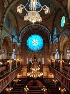 View of the interior of Eldridge Street Synagogue from the second floor, looking down. Pews and lights can be seen on the bottom floor. Two chandeliers hang overhead. The walls are painted, and pews can also be seen on the second floor. A large, blue, circular window is visible on the far wall.