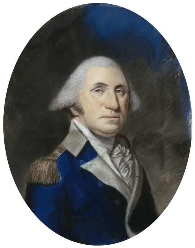 A man with white hair wearing a blue coat sits in three-quarter view against a gray background.